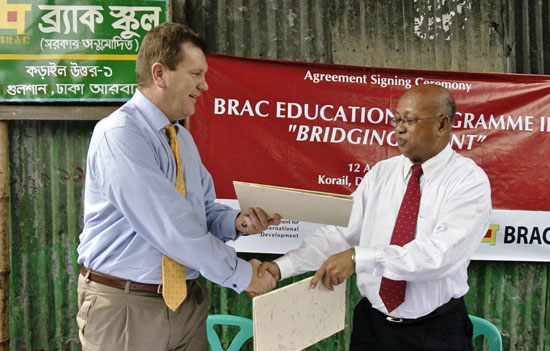 DFID Country Representative Chris Austin and BRAC Executive Director Dr. Mahabub Hossain sign the agreement in a BRAC Primary school yard at Korail Slum, Gulshan